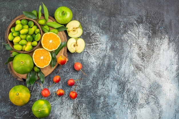 Draufsicht aus der ferne früchte die appetitlichen äpfel zitrusfrüchte auf dem schneidebrett kirschen