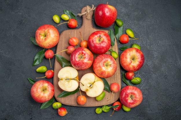 Draufsicht aus der ferne früchte die appetitlichen kirschen äpfel auf dem brett neben den zitrusfrüchten