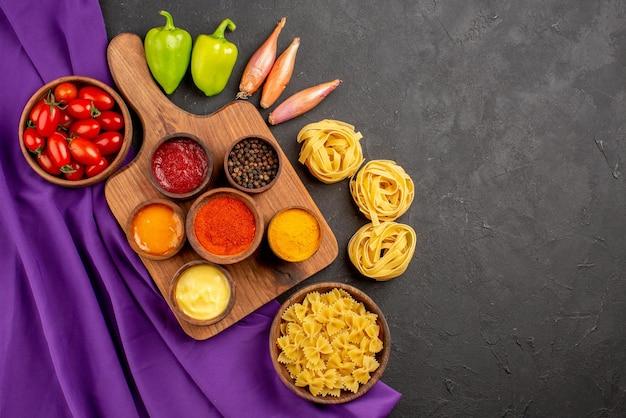 Draufsicht aus der ferne gewürze und nudeln drei arten von gewürzen und saucen auf dem holzbrett neben der schüssel mit nudeln grüne kugelpfefferzwiebel und tomaten auf der lila tischdecke auf dem dunklen tisch
