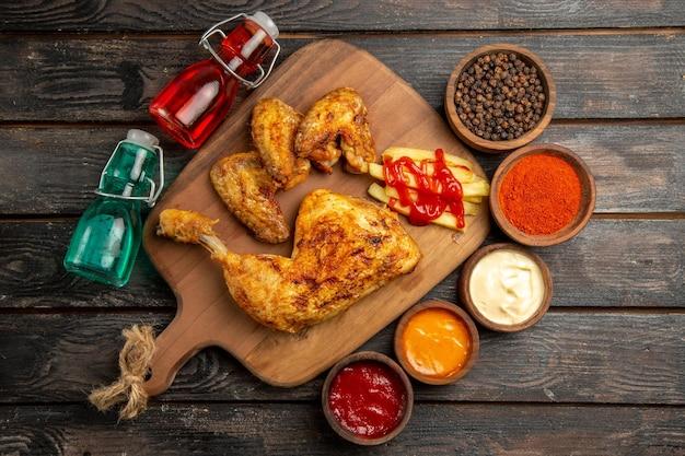 Draufsicht aus der ferne hühnerrote und blaue flaschen neben dem huhn mit pommes frites und ketchup auf dem schneidebrett schalen mit schwarzen pfeffersaucen gewürzen