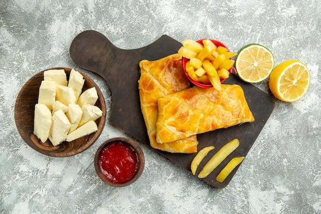 Draufsicht aus der ferne käse-pommes-frites-schale mit käse-ketchup-zitrone und pommes-frites und appetitlichen kuchen auf dem küchenbrett auf dem grauen tisch