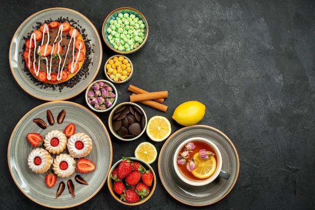 Draufsicht aus der ferne kuchen mit süßigkeiten kuchen mit erdbeer-schwarztee mit zitronenteller mit keksen mit erdbeer-hizelnüssen schalen mit schokolade und verschiedenen süßigkeiten auf der linken seite des dunklen tisches