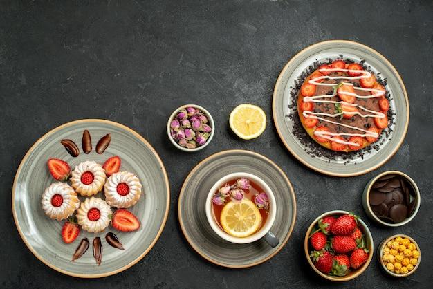 Draufsicht aus der ferne kuchen mit süßigkeiten kuchen mit erdbeere auf weißem teller schwarzer tee mit zitronenteller kekse mit erdbeer-hizelnuss-schalen mit schokolade und verschiedenen süßigkeiten auf schwarzem tisch