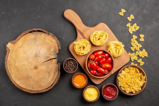Draufsicht aus der ferne nudeln auf dem brett schüsseln mit tomaten und nudeln auf dem schneidebrett neben dem holzbrett und verschiedene saucen gewürze nudeln auf dem tisch