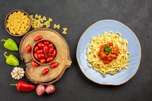 Draufsicht aus der ferne pasta und tomaten teller pasta mit fleisch braune schüssel tomaten auf dem holzbrett pasta und zwiebel paprika und knoblauch auf dem tisch