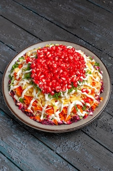 Draufsicht aus der ferne salat mit granatapfel weihnachtssalat mit mayonnaise-samen von granatapfel und rüben in der platte auf dem holztisch