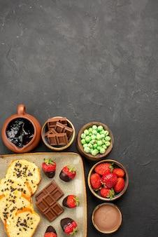 Draufsicht aus der ferne schokoladen-erdbeer-kuchen schokoladen-erdbeeren grüne bonbons und schokoladencreme in schüsseln appetitlicher kuchen und erdbeeren auf dem dunklen tisch