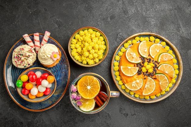 Draufsicht aus der ferne süßigkeiten auf dem teller ein teller mit cupcakes und eine schüssel mit süßigkeiten auf der blauen untertasse eine tasse tee mit zimtkuchen mit orangefarbenen schüsseln mit gelben süßigkeiten auf dem schwarzen tisch