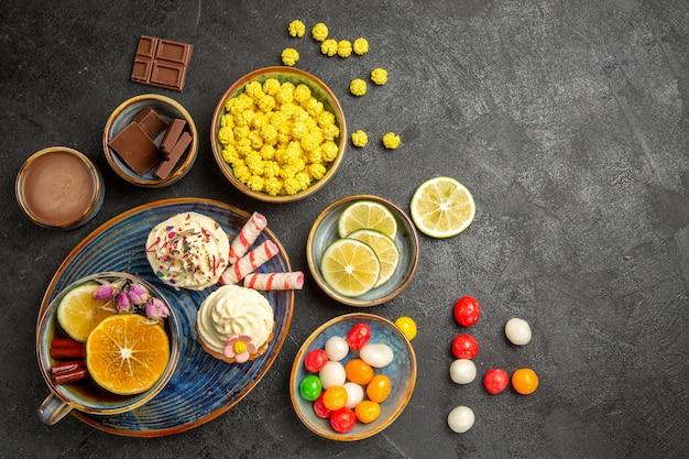 Draufsicht aus der ferne süßigkeiten auf dem tisch cupcakes und eine tasse tee mit zitrone auf der untertasse schalen mit schokoladen-limettenschokoladencreme bunte süßigkeiten auf dem dunklen tisch