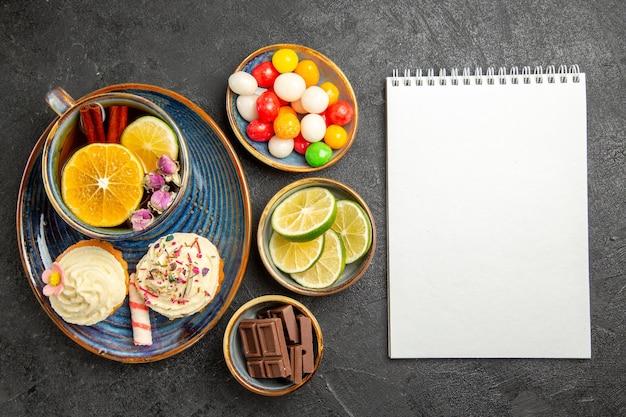 Draufsicht aus der ferne süßigkeiten auf dem tisch drei schalen bonbons schokolade und limettenscheiben neben dem weißen notizbuch zwei cupcakes und die tasse kräutertee auf dem tisch