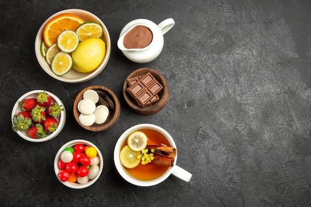 Draufsicht aus der ferne süßigkeiten auf dem tisch eine tasse tee mit zimt und zitrone und schalen mit erdbeerschokolade und bonbons auf dem dunklen tisch