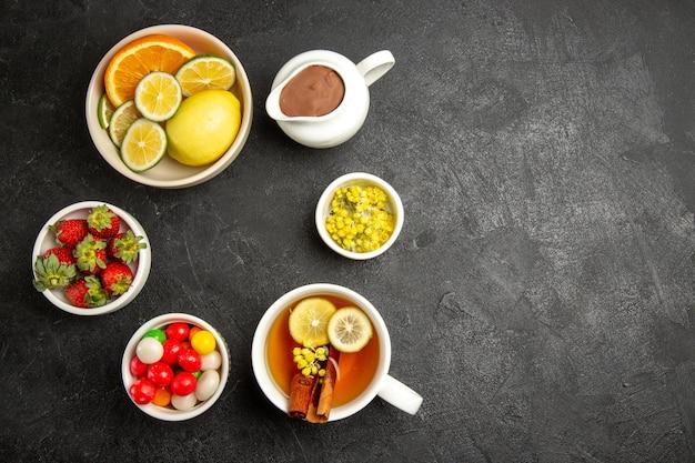 Draufsicht aus der ferne süßigkeiten auf dem tisch schüsseln mit erdbeeren und kräutern und eine tasse tee mit zitronen- und zimtstangen