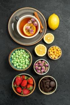 Draufsicht aus der ferne süßigkeiten mit tee schwarzer tee mit zitronen-hizelnuss-schalen mit schokolade und verschiedenen süßigkeiten in der tischmitte