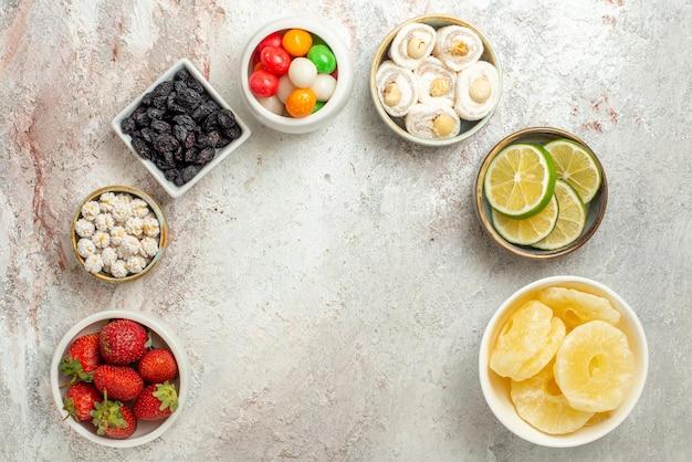 Draufsicht aus der ferne süßigkeiten schalen mit beeren süßigkeiten und getrocknete ananas sind in einem kreis ausgelegt