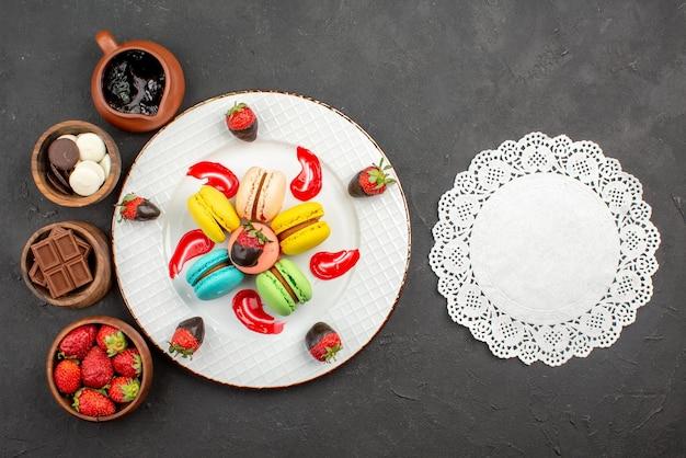 Draufsicht aus der ferne süßspeiseteller mit makronen und vier schalen mit süßigkeiten, schokoladenerdbeeren und schokoladencreme neben dem spitzendeckchen auf dunklem hintergrund