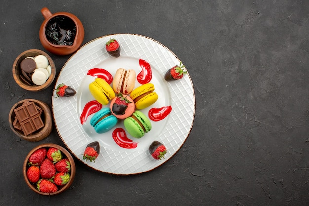 Draufsicht aus der ferne süßspeiseteller mit makronen und vier schüsseln mit süßigkeiten, schokoladenerdbeeren und schokoladencreme auf dunklem hintergrund