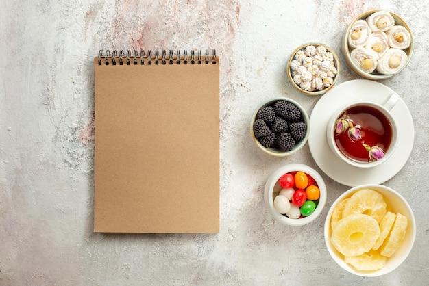 Draufsicht aus der ferne tasse tee-creme-notizbuch neben der tasse tee und schalen mit verschiedenen süßigkeiten getrocknete ananas türkische freude auf dem weißen hintergrund