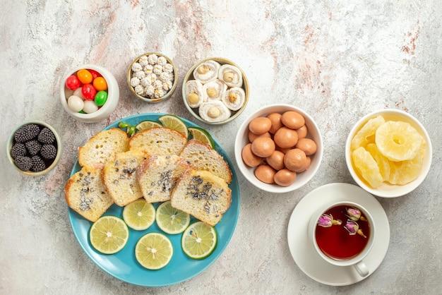 Draufsicht aus der ferne tasse tee weiße tasse tee und schüsseln mit appetitlichem türkischem genuss und getrockneten ananas neben dem kuchenteller und geschnittenen limetten auf dem tisch