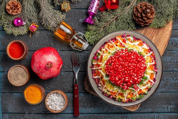 Draufsicht aus der ferne teller in der tellerschale mit granatapfel auf dem brett neben den gewürzschalen flasche ölgabel granatapfel und äste mit zapfen und weihnachtsbaumspielzeug