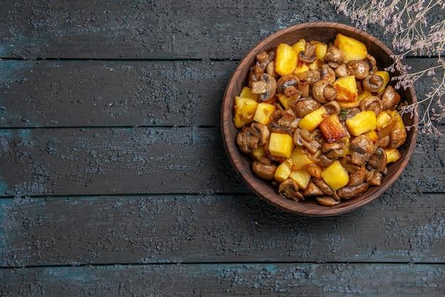 Draufsicht aus der ferne teller mit essen braune schüssel mit kartoffeln und pilzen neben den ästen rechts vom tisch