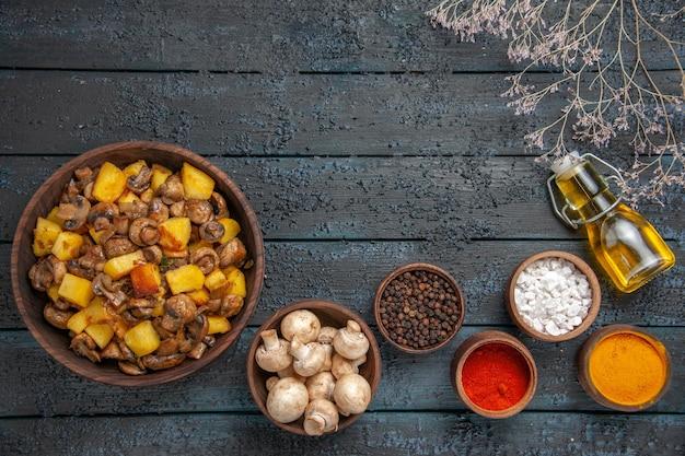 Draufsicht aus der ferne teller mit kartoffeln und pilzen neben einer schüssel mit weißen pilzen, bunten gewürzen und öl in der flasche