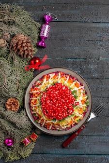 Draufsicht aus der ferne weihnachtsteller weihnachtsteller gabel und fichtenzweige mit zapfen und weihnachtsbaumspielzeug