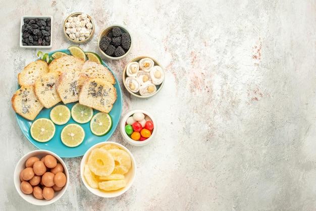 Draufsicht aus der ferne zitronenkuchen sieben schüsseln mit bonbons neben dem teller mit kuchenstücken mit zitrone auf dem tisch