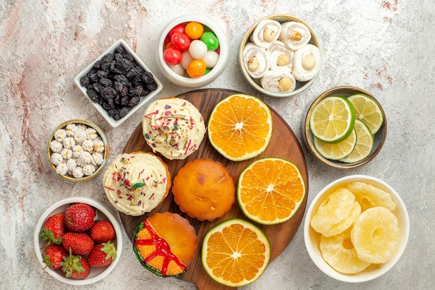 Draufsicht aus der ferne zitrusfrüchte auf dem brett schalen mit beerenbonbons und getrockneten ananas und geschnittenen orangen und keksen auf dem holzbrett