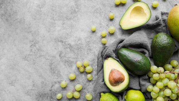Draufsicht avocado und trauben mit kopierraum