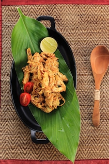 Draufsicht ayam suwir bumbu kuning (ayam sisit mit gelbem gewürz) ist eine balinesische oder indonesische küche, die aus hühnchenfleischstücken hergestellt wird. auf schwarzer ovaler platte serviert, platz für text oder rezept kopieren