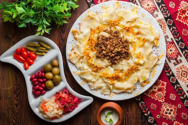 Draufsicht azerbaijani guru khingal kaukasische nudeln mit gebratenem gehacktem fleisch und zwiebeln mit sauerrahmsauce und gurken auf einer tischdecke horizontal