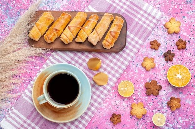Draufsicht bagels und kekse mit tasse tee auf dem rosa schreibtisch.