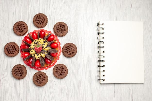 Draufsicht-beerenkuchen auf dem roten ovalen spitzendeckchen, abgerundet mit keksen und einem notizbuch auf dem weißen holztisch