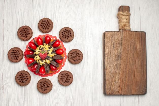 Draufsicht-beerenkuchen auf dem roten ovalen spitzendeckchen, abgerundet mit keksen und einem schneidebrett auf dem weißen holztisch