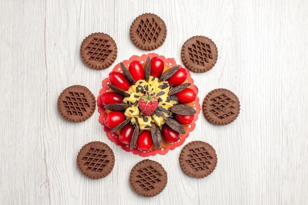 Draufsicht-beerenkuchen auf dem roten ovalen spitzendeckchen und kekse auf dem weißen holztisch
