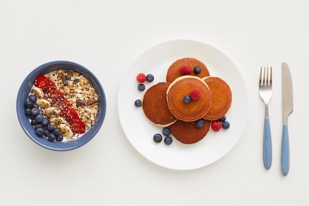 Draufsicht bei minimaler zusammensetzung der köstlichen goldenen pfannkuchen, die mit frischen beeren neben müsliteller verziert werden, gesundes frühstückskonzept
