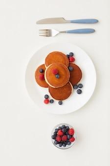 Draufsicht bei minimaler zusammensetzung der köstlichen goldenen pfannkuchen, die mit frischen beeren neben parfait-tasse verziert werden, gesundes frühstückskonzept