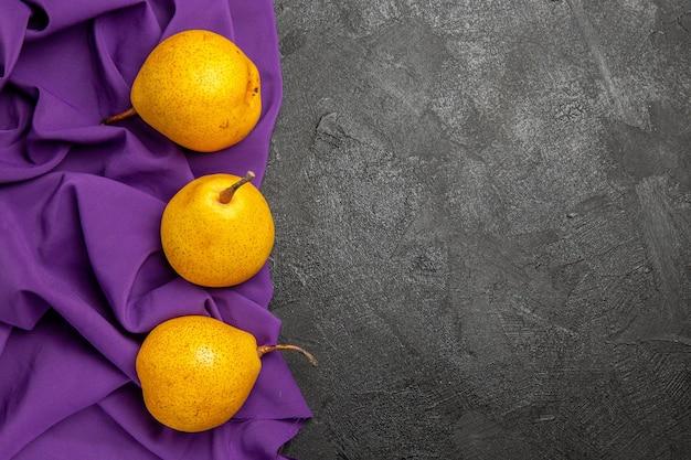 Draufsicht birnen auf der tischdecke drei gelbe birnen auf der lila tischdecke auf der linken seite des dunklen tisches
