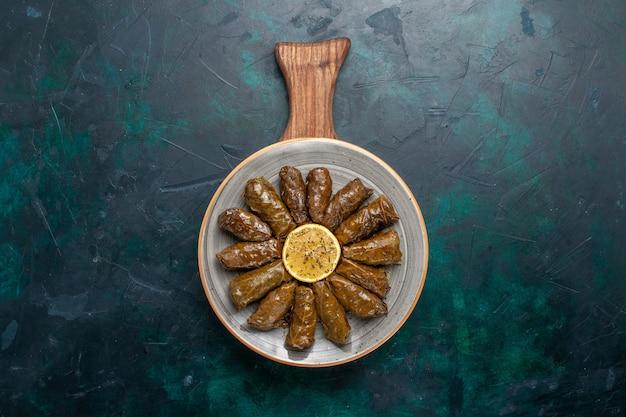 Draufsicht blatt dolma köstliche östliche fleischmahlzeit, die innerhalb der grünen blätter auf dem dunkelblauen schreibtischfleischmahlzeitnahrungsmittelessen-gemüsegesundheitskalorie gerollt wird