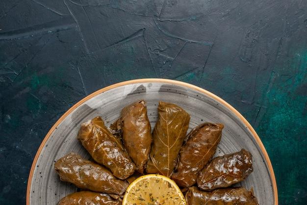 Draufsicht blatt dolma köstliche östliche fleischmahlzeit, die innerhalb der grünen blätter auf dem dunkelblauen schreibtischfleischmahlzeitnahrungsmittelessen-gemüsegesundheitskalorien gerollt wird