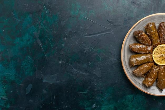 Draufsicht blatt dolma köstliche östliche fleischmahlzeit, die innerhalb der grünen blätter auf dunkelblauem schreibtischfleischmahlzeitnahrungsmittelessengemüsegesundheitskaloriengericht gerollt wird