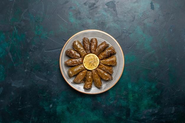 Draufsicht blatt dolma köstliche östliche fleischmahlzeit gerollt in grünen blättern auf dem dunkelblauen schreibtisch fleischmahlzeit essen abendessen gemüse gesundheit kalorien