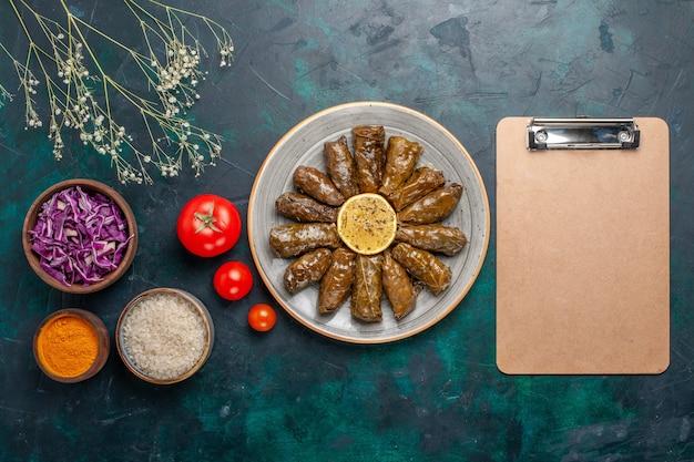 Draufsicht blatt dolma köstliche östliche fleischmahlzeit rollte in grünen blättern mit frischen tomaten auf blauem hintergrund fleischnahrung abendessen abendessen gemüsegesundheit
