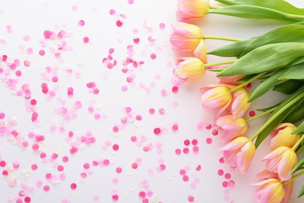 Draufsicht-blumenhintergrund von rosa tulpen und konfetti mit kopienraum