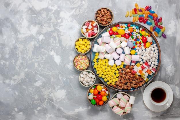 Draufsicht bonbon zusammensetzung verschiedenfarbige bonbons mit marshmallow und tee auf weißen schreibtisch zucker bonbon bonbon süße confitures