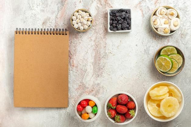 Draufsicht bonbons in schalen scheiben von beeren getrocknete ananas und turkish delight neben dem cremefarbenen notizbuch auf dem tisch