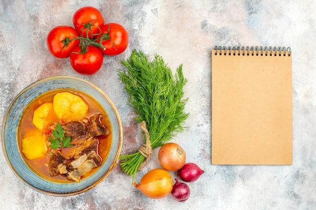 Draufsicht bozbash-suppe ein bündel dilltomaten zwiebeln ein notizbuch auf nacktem hintergrund