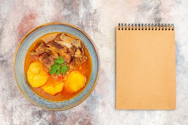 Draufsicht bozbash-suppe ein notizbuch auf nacktem hintergrund