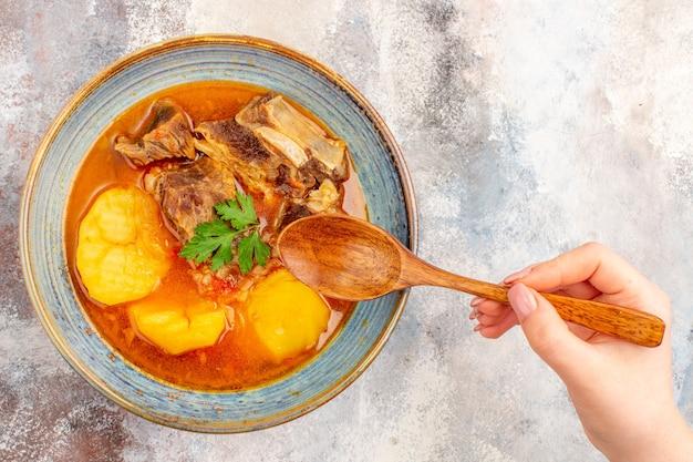 Draufsicht bozbash-suppe in einer schüssel ein holzlöffel in weiblicher hand auf nacktem hintergrund