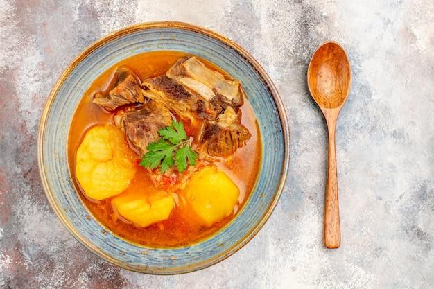 Draufsicht bozbash-suppe in einer schüssel ein löffel auf nacktem hintergrund